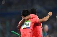 陸上男子400メートルリレー決勝で2位になり、抱き合って喜ぶ桐生祥秀(左)とケンブリッジ飛鳥=リオデジャネイロの五輪スタジアムで2016年8月19日、三浦博之撮影