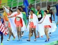 陸上男子400メートルリレー決勝で1位となったジャマイカのウサイン・ボルト(奥右から3人目)らの前で喜び合う2位の(手前左から)山県亮太、飯塚翔太、ケンブリッジ飛鳥、桐生祥秀ら日本の選手たち=リオデジャネイロの五輪スタジアムで2016年8月19日、梅村直承撮影
