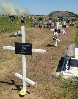 「身元不明戦士」と記された墓標がいくつも並ぶ墓地。ロシア軍人が秘密裏に埋葬されている可能性が高いとされる=ウクライナ東部ドネツク郊外で7月16日、真野森作撮影