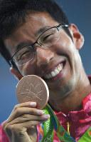 男子50キロ競歩決勝で銅メダルを獲得し、表彰式で笑顔を見せる荒井広宙=リオデジャネイロの五輪スタジアムで2016年8月19日、三浦博之撮影