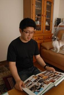 「34歳で入学したけど、見た目は他の学生と変わらないかも」。大学時代のアルバムを眺める小山公一郎さん=埼玉県内で2016年8月20日、坂根真理撮影