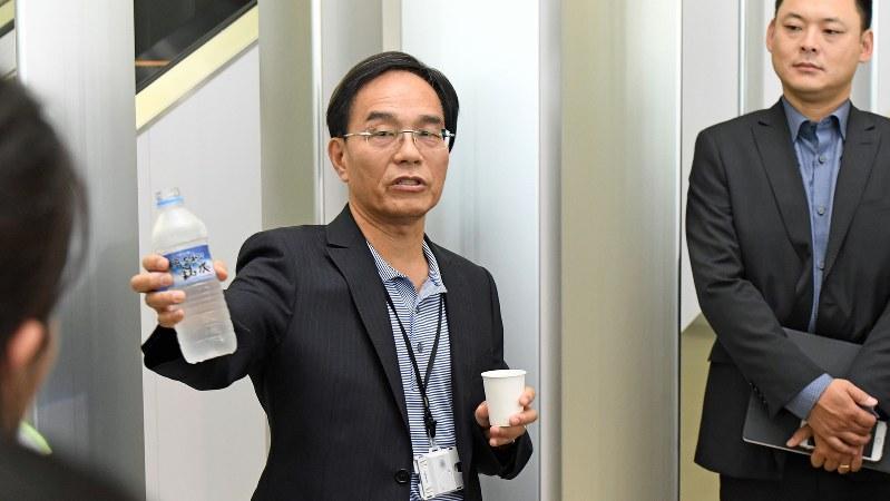 ペットボトルの水を使って業績改善の説明をする戴正呉・シャープ社長=2016年8月22日、川平愛撮影