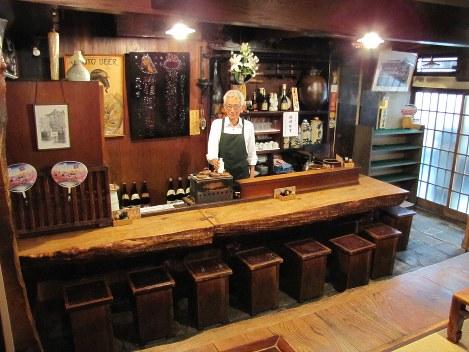酒屋時代からの歴史が詰まった鍵屋の店内と7代目店主、清水賢太郎さん=台東区根岸3で