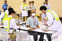 放射線量を測定するスクリーニングを受ける訓練参加者=福井県南越前町鋳物師の南条勤労者体育センターで、竹内望撮影