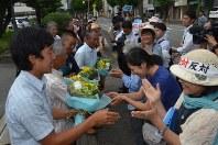 和解が成立し、支援者から花束を受け取る元被告の住民ら