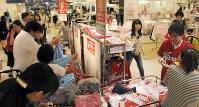 カープ応援セールの商品に手を取る買い物客=広島市中区のそごう広島店で2016年8月31日、東久保逸夫撮影