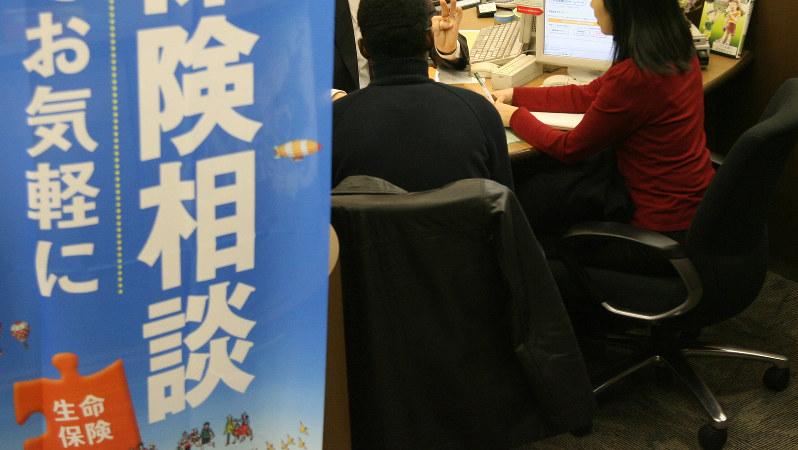 保険商品について説明する銀行員=2007年12月、佐々木順一撮影