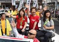 祝勝パレードで沿道の声援に応える吉田沙保里選手(左)、登坂絵莉選手(右)ら=愛知県大府市で2016年9月3日午前9時38分、木葉健二撮影