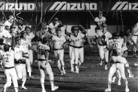 1984年度日本シリーズ[広島東洋カープ・阪急ブレーブス第7戦]4勝3敗で広島が優勝した瞬間ベンチから大喜びで飛び出す広島ナインと、抱き合う山根和夫投手・達川光男捕手のバッテリー(右端)=広島市民球場で1984年10月22日撮影