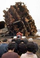 謎の爆沈から28年、引揚げられた「陸奥」の艦尾の前で、慰霊する遺族ら =1971年3月撮影
