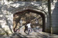 千代田区にあった旧キャンパスの象徴だった「南門(白門)」を模したモニュメントを押す土屋さん=八王子市内で