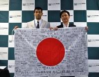8月に行われた、あいおいニッセイ同和損保の壮行会。宮崎哲(左)には社員が激励の言葉を書き込んだ日の丸が贈られた=東京都渋谷区で、飯山太郎撮影