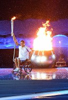 Six-time Paralympic champion swimmer Clodoaldo Silva of Brazil holds up the Paralympic torch after lighting the Paralympic flame at the opening ceremony of the 2016 Paralympics at Maracana Stadium in Rio de Janeiro on Sept. 7, 2016. (Mainichi)