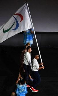 パラリンピックのシンボル、スリー・アギトスの旗を掲げて入場する難民選手団=リオデジャネイロのマラカナン競技場で2016年9月7日午後6時44分、徳野仁子撮影