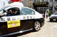 特殊詐欺防止を訴えるシートをドアに貼ってパトロールに出発するパトカー=和歌山市来栖の和歌山東署で、最上和喜撮影