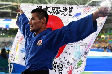 柔道(視覚障害)男子66キロ級で銅メダルを獲得し、メッセージが書き込まれた日の丸を掲げる藤本聡=リオデジャネイロのカリオカアリーナで2016年9月8日、徳野仁子撮影