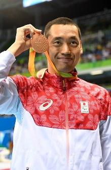 競泳男子100メートル背泳ぎ(知的障害)で3位となり、銅メダルを掲げる津川拓也=リオデジャネイロの五輪水泳競技場で2016年9月8日、徳野仁子撮影