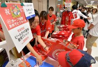 【広島優勝セール】広島の選手がビールかけの際に着用したモデルのTシャツを買い求める人たち=広島市中区で2016年9月11日午前10時33分、山田尚弘撮影