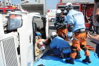 多重事故を想定して、横転した車から負傷者を救出する消防署員ら