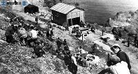 礼文島金環食。アメリカ地理学協会、東京天文台の日米共同観測所を見学の小学生と村民ニュースのカメラマン。起登臼で=1948(昭和23)年5月撮影