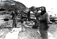 礼文島金環食。ガラス片で見る起登臼の漁民=1948(昭和23)年5月9日撮影