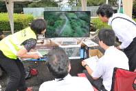 ドローンから送られた映像を見ながら下校児童の様子を確認する関係者=富士見町で