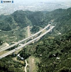 東海道新幹線と交差する東名高速道路。東京側から新幹線の袖師トンネル(中央)、東名高速の袖師トンネル(右側)を見る。後方は清水市街(現在の静岡市清水区)=1970年(昭和45年)5月22日、本社ヘリから撮影