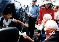 東名高速道路開通:秋の交通安全運動が始まり、安全運転を呼びかけるチラシを自動車に配る一日高速隊長の成田きんさん(右手前)と蟹江ぎんさん=東名高速道・上郷サービスエリアで1997年(平成9年)9月21日撮影