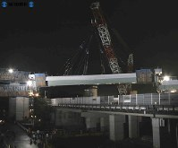 第二東名高速道路の建設工事で東名高速道路をまたぐ巨大な橋げたを架ける工事。国内最大級のクレーンが使われ、既にできている道路と橋げたとのすきまは両側ともたった6ミリ。近くの住民が見守る中、慎重な作業が行われた=2006年(平成18年)11月11日撮影