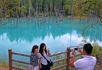 元の状態に戻り、立ち入りが可能となった「青い池」で、記念写真を撮る観光客ら=北海道美瑛町で2016年9月14日午前11時31分、手塚耕一郎撮影