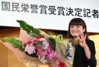 国民栄誉賞の受賞が決まり、記者会見で花束を手に笑顔の伊調馨選手=東京都新宿区で2016年9月13日午後4時33分、宮間俊樹撮影