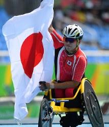 陸上男子1500メートル(車いすT52)で銀メダルを獲得し日の丸を掲げる佐藤友祈=リオデジャネイロの五輪スタジアムで2016年9月15日、徳野仁子撮影