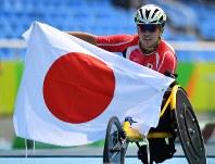 陸上男子1500メートル(車いすT52)で銀メダルを獲得し、日の丸を広げる佐藤友祈=リオデジャネイロの五輪スタジアムで2016年9月15日、徳野仁子撮影