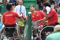 車いすテニス男子ダブルス3位決定戦、日本人ペア同士の対戦となり、終了後三木拓也(左手前)と握手を交わす国枝慎吾(右から2人目)=リオデジャネイロの五輪テニスセンターで2016年9月15日、徳野仁子撮影