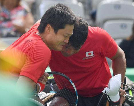 車いすテニス男子ダブルスで銅メダルを獲得し、泣きながら抱き合う国枝(左)と斎田=徳野仁子撮影