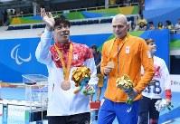 競泳男子200メートル個人メドレー(知的障害S14)で銅メダルを獲得し観客席に向かって笑顔で手を振る中島啓智(左)=リオデジャネイロの五輪水泳競技場で2016年9月17日、徳野仁子撮影