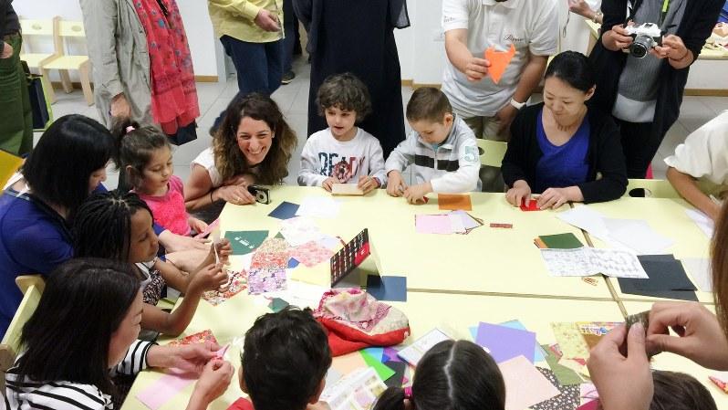 イタリアの保育園で園児たちと交流する研修参加者たち=ポピンズ提供