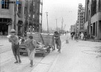 【広島】広島電鉄の軌道を使って運ばれる復旧資材。右は福屋百貨店、その奥に中国新聞社=1945(昭和20)年9月