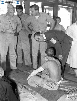 【広島】原爆の被害状況を調査する米陸軍調査団。被爆者と話すのは案内を務めた都築正男東大教授=広島県大野村(当時)の大野浦陸軍病院で1945(昭和20)年9月10日