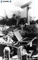 【長崎】半分残った鳥居のそばで壊れた住宅を片付ける住民=1945(昭和20)年8月