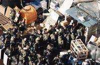 オウム真理教の施設に入る捜査員たち=旧山梨県上九一色村のオウム施設で、本社ヘリから1995年3月22日撮影