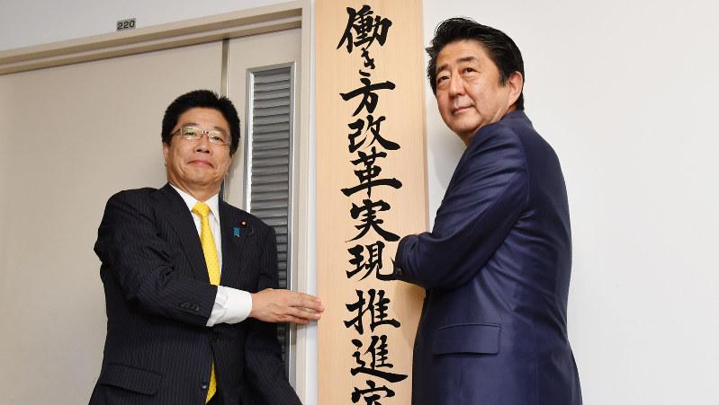 「働き方改革実現推進室」の看板をかける安倍首相と加藤働き方改革相=2016年9月2日、代表撮影