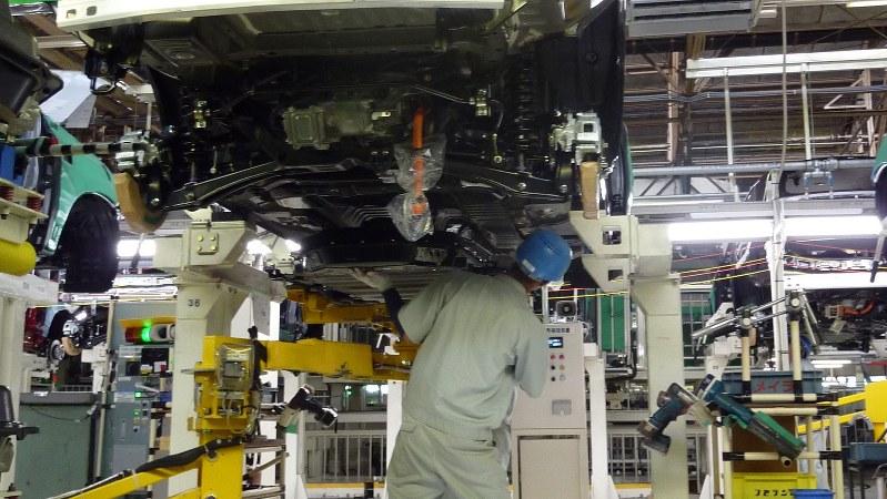 三菱自動車・岡崎工場の生産ラインで車体を組み立てる作業員=2014年6月、和田憲二撮影