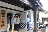 和田湯入り口に設置した防犯カメラを鈴木署長(右端)に指し示す植松区長(右から2人目)=伊東市竹の内2で