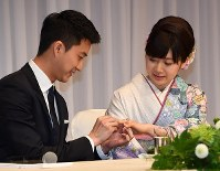 Chiang Hung-chieh, left, places a wedding ring on Ai Fukuhara's finger during a news conference in Tokyo's Minato Ward on Sept. 21, 2016, to announce their marriage. (Mainichi)