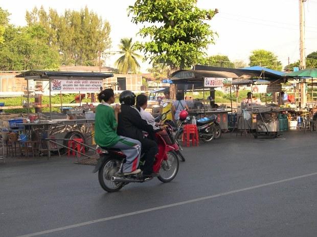 ロッブリー駅前ののどかな風景。線路沿いには屋台が並び、その前をバイクが走る。この街ではバイクを3人乗りしていても、警察はとがめない=04年7月、筆者撮影