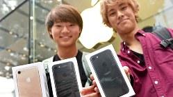 購入したiPhone 7や7 Plusを手に笑顔を見せる大学生=東京都渋谷区のアップルストア表参道店で、竹内紀臣撮影