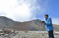 御嶽山の噴火から2年が経ち、弟夫妻を亡くした猪岡孝一さん。弟が持っていたカメラを手に山頂付近を見つめていた=長野県木曽町で2016年9月27日午前11時20分、宮間俊樹撮影