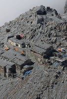 御嶽山噴火から2年。山頂付近の御嶽神社と山荘は火山灰に覆われていた=2016年9月27日午前11時31分、本社ヘリから長谷川直亮撮影