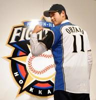 背番号11のユニホームを着てこぶしを握る大谷翔平。日本ハムからは投手と打者の「二刀流」育成プランが提示されており、「投手としても打者としても日本一を目指し、チームに貢献したい」と思いを込めた=札幌市内で2012年12月25日、梅田麻衣子撮影